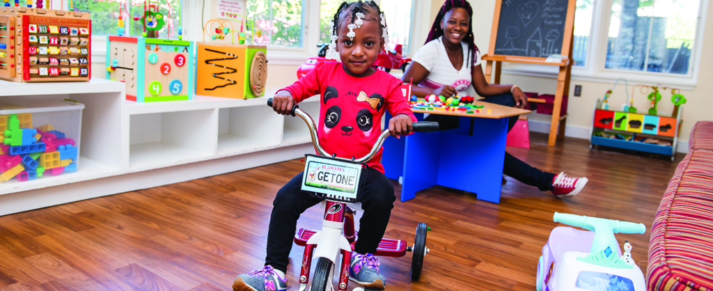 young girl on tricycle playing in playroom while mother watches in background