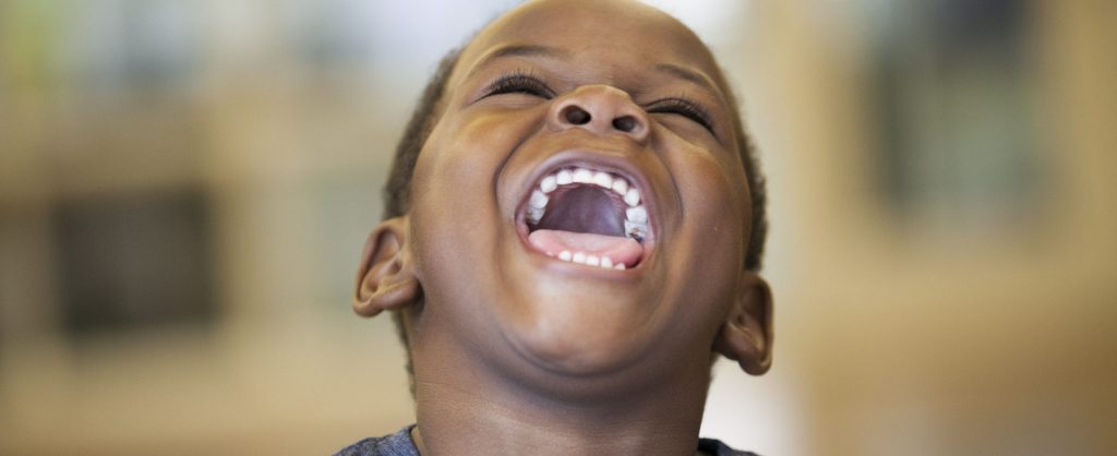 young african american child smiling widely expressing joy