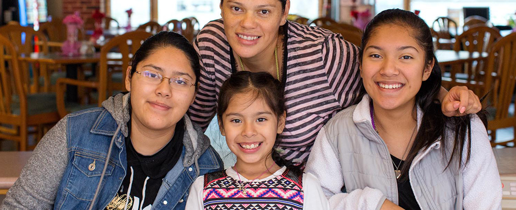 mother and her three daughters grouped together in a dining room smiling