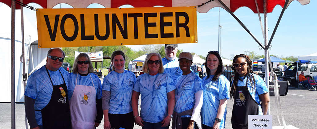 group of smiling volunteers in matching blue tie-dye shirts working for a fundraising event