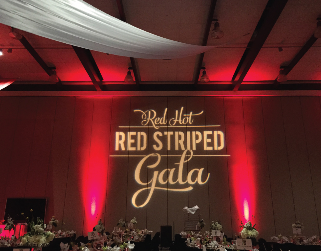 red hot red striped gala with red uplighting ballroom decoration