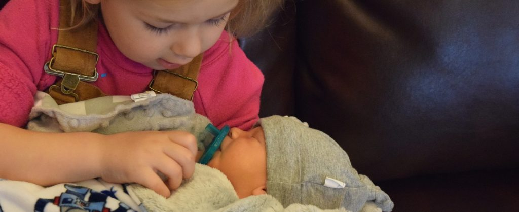 young girl lovingly holding infant sibling
