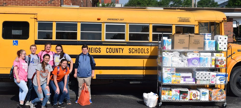 group of people standing in front of school bus with a large shelving cart full of donated goods